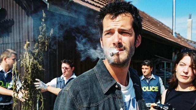 Da steht ein Mann mit Joint im Mund, dahinter räumt die Polizei Hanfpflanzen weg.