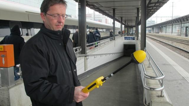 Markus Gugler mit seinem gelben Messgerät mit einer Art Mikrofon am Bahnhof-Perron in Aarau.