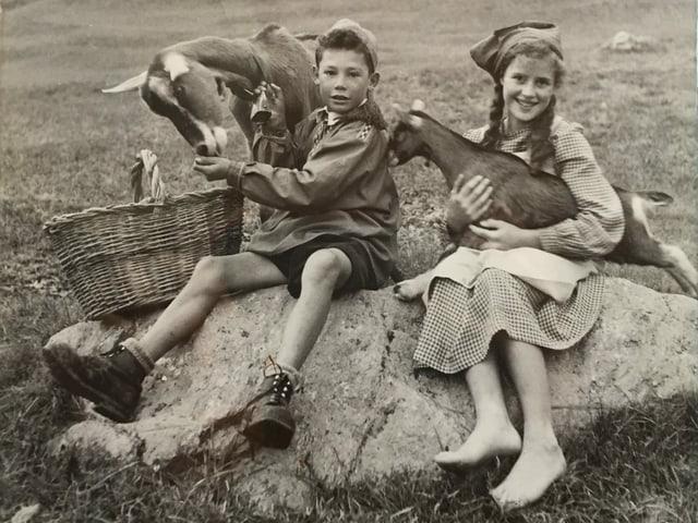 Junge und Mädchen mit Geissen im Arm