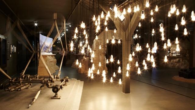 Ausstellungsraum, der von vielen Glühbirnen, die von der Decke hängen, beleuchtet wird.