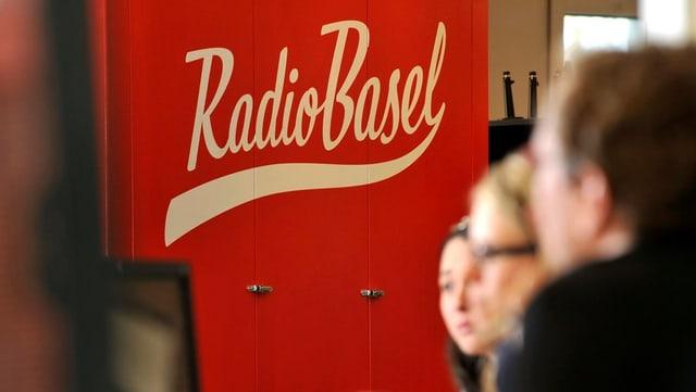 Mehrere Personen an einer Sitzung vor dem Radio Basel Logo