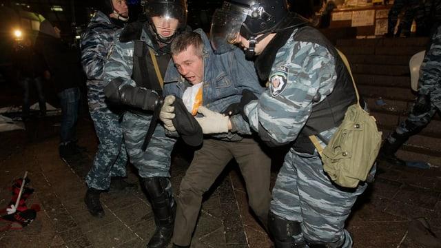 Ukrainische Polizisten nehmen einen Aktivisten fest.