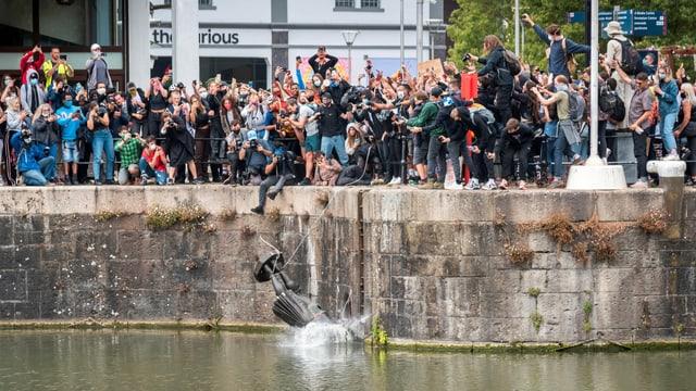 Statue wird ins Meer geworfen, Demonstranten sehen zu.