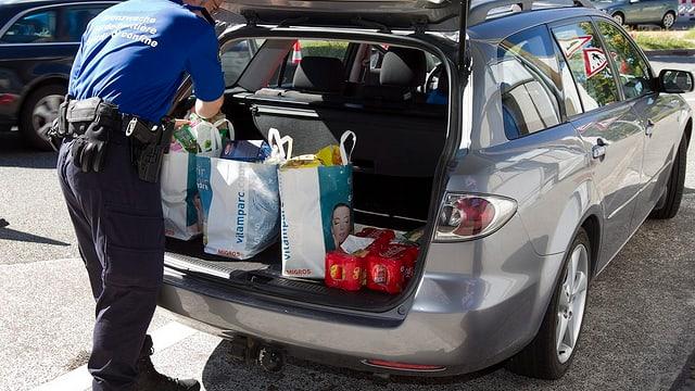 Zöllner kontrolliert Einkaufstaschen im Kofferraum eines silbergrauen Kombis.