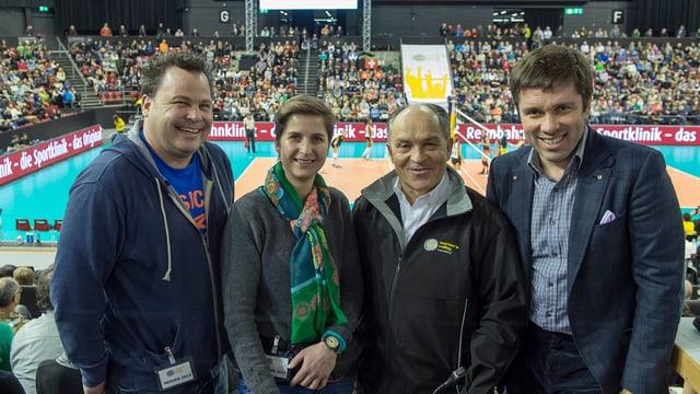Drei Männer und eine Frau, im Hintergrund ein Volleyball-Feld und volle Zuschauerränge