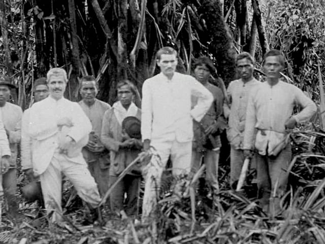 Schwarz-Weiss-Fotografie: Zwei weisse Männer posieren mit einer Gruppe einheimischer Männer im Busch.