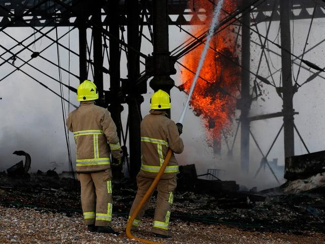 Zwei Feuerwehrleute spritzen Wasser auf den Pier