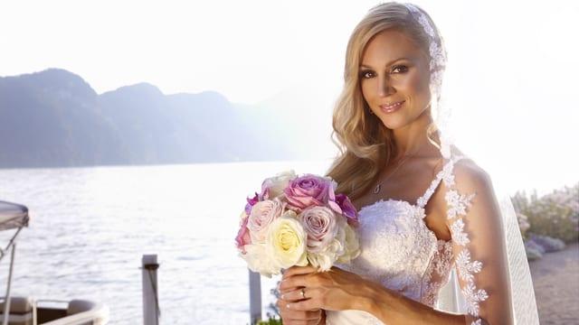 Porträt: Jennifer Ann Gerber im weissen Hochzeitklaid. Sie hält ihren rosa Brautstrauss und trägt einen Schleier.