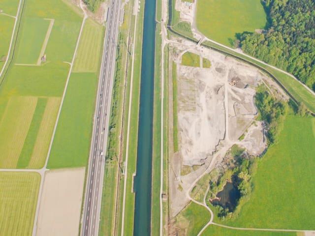 Luftaufnahme, Fluss, daneben eine Art Dreieck mit Dreck.