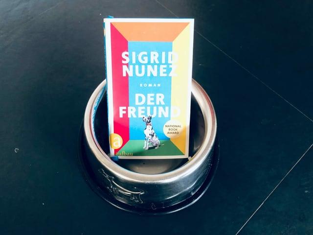 Der Roman «Der Freund» von Sigrid Nunez steht in einem Hundefutternapf