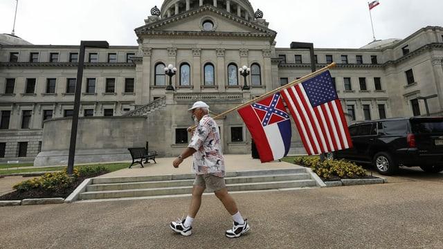 Ein Mann mit einer Flagge Mississippis und der US-Flagge