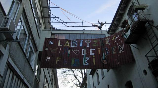 """Zwei Gebäude, dazwischen ein Banner mit der Aufschrift """"wir bleiben farbig"""""""