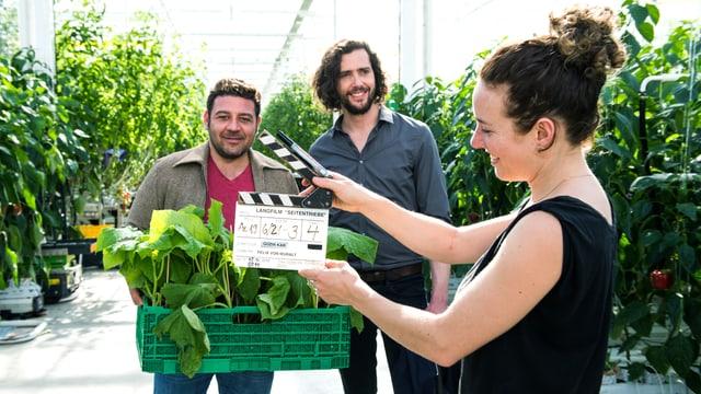 Zwei Männer in einer Gärtnerei, einer hält einen Korb mit Grünzeug in der Hand. Davor die Frau mit der Filmklappe.