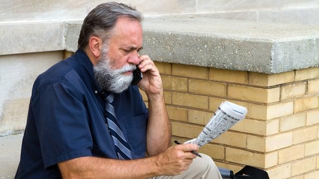 Mann mit Zeitung an Handy