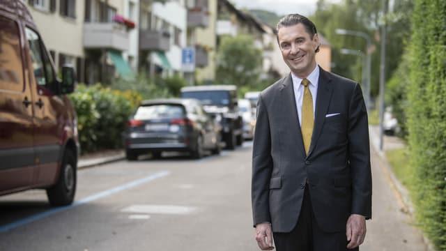 Martin Suter steht auf einer Strasse und lächelt in die Kamera.