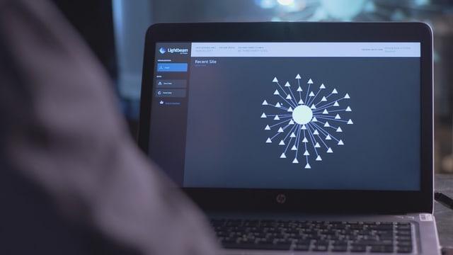 Notebook-Monitor mit einem Kreis in der Mitte, das ist eine Website, vom Kreis weg führen dutzende Linien, jede stellt einen Tracker dar.