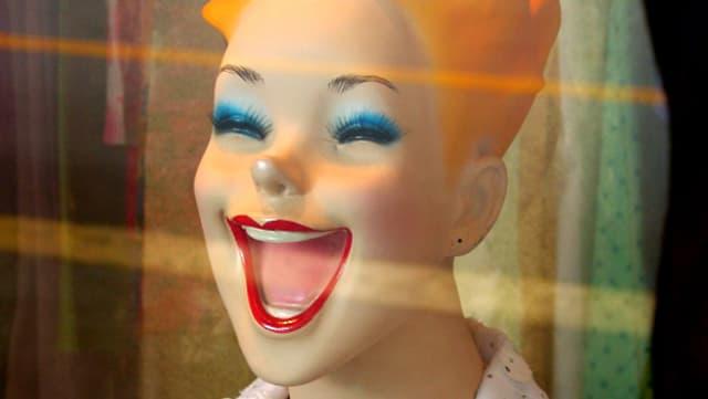 Eine stark lachende Schaufensterpuppe mit weit aufgerissenem Mund.