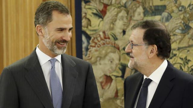 König Felipe (links) und Mariano Rajoy (rechts) lächeln sich an.