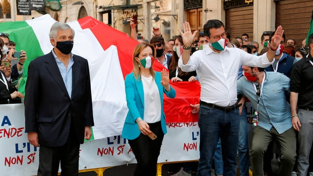 Tajani, Meloni und Salvini mit Mund- und Nasenschutz stehen vor einer italienischen Flagge auf einer Strasse mit anderen Demonstranten.