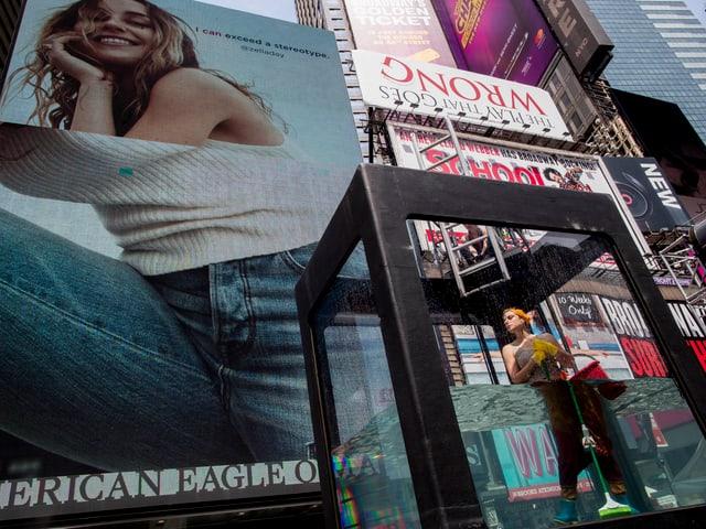 Künstler im Wassertank, im Hintergrund Werbeplakate.