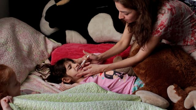 Mutter flösst einem Mädchen mit Spritze Medikament in den Mund.