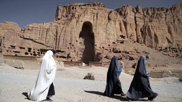 Frauen in Burkas laufen an dem Loch im Fels vorbei, wo einst die Buddhastatuen standen.