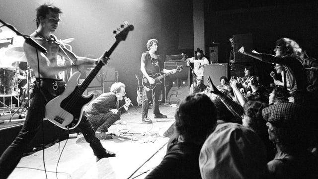Eine Punk-Band steht auf der Bühne, ein Mann im Publikum macht ein Foto.