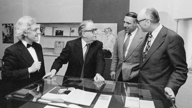 Vier Männer stehen vor einer Vitrine mit Dokumenten und diskutieren.