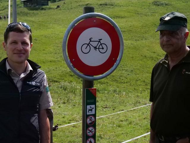 Zwei Männer vor einer Verbotstafel für Biker.