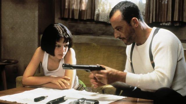 Junges Mädchen sieht einem Mann zu wie er eine Waffe lädt
