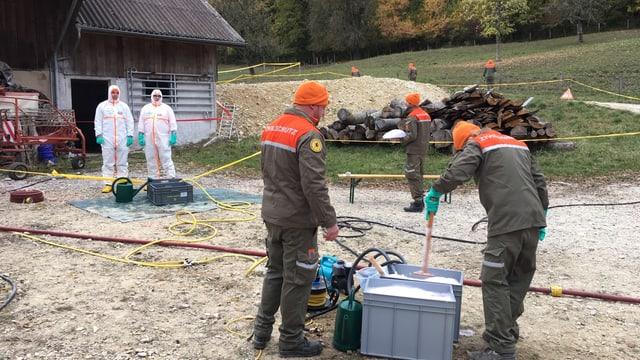 Zivilschutzer bereiten auf einem Bauernhof Desinfektionsmittel vor.