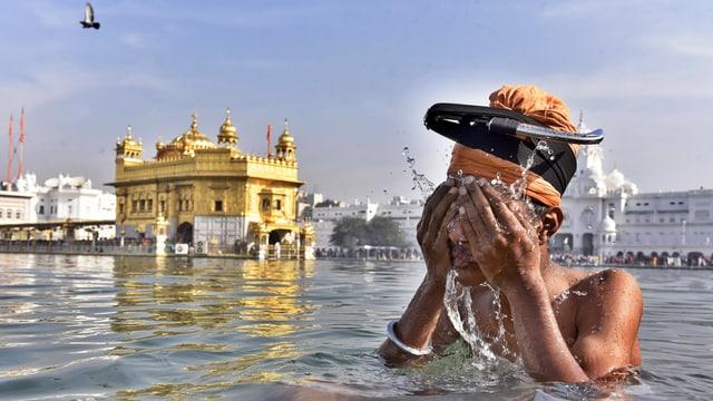 Ein Sikh nimmt ein rituelles Bad, im Hintergrund der Goldene Tempel von Amritsar.