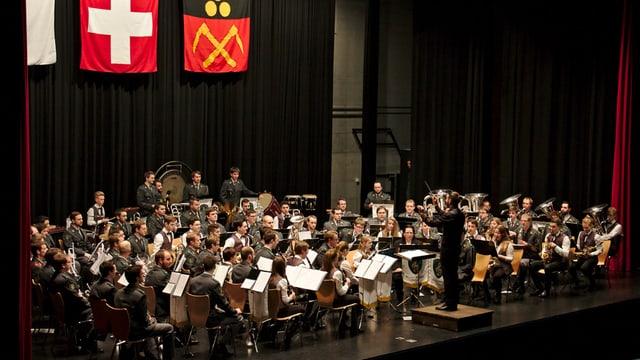 Ein grosses Orchester mit Dirigent auf einer Bühne.