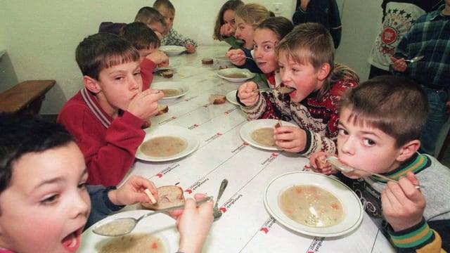 Schulkinder löffeln ihre Mittagssuppe an einem grossen Tisch.