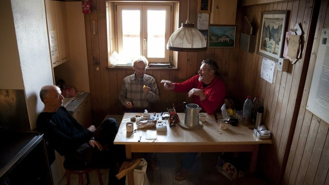 Drei Männer sitzen in einer kleinen Stube an einem Holztisch