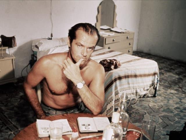 Jack Nicholson sitzt mit nacktem Oberkörper in einem Zimmer.