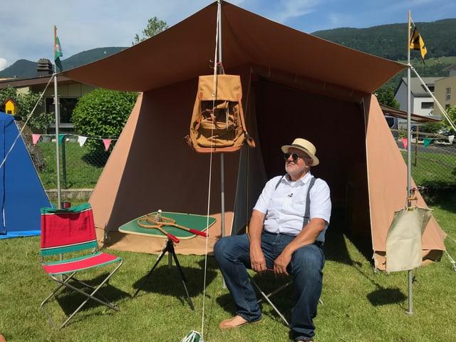 Ein Mann sitzt vor einem Retro-Zelt.