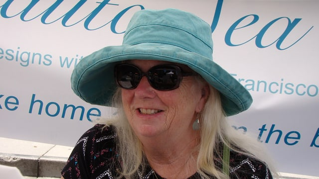 Eine ältere Frau mit hellblauem Hut.