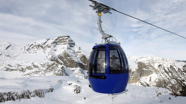 Eine blaue Gondel vor einer bergigen Winterlandschaft.