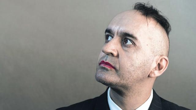 Ein Mann mit pinkfarbenem Lippenstift und schwarzem Kamm.