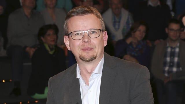 Mann mit Kinnbart und Brille.