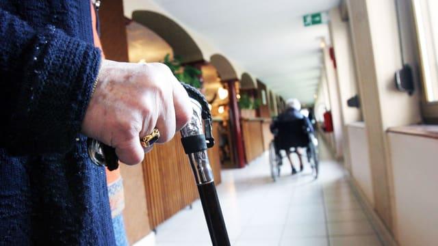 Hand einer älteren Dame mit silbrig verziertem Gehstock. Sie geht einen Gang entlang. Etwas weiter unten ist eine Person im Rollstuhl.