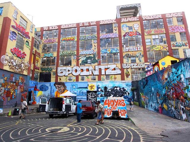 Grosses Gebäude, das komplett mit Grafittis besprayt ist.