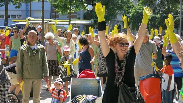 Eine Gruppe von Personen, die ihre Arme in die Höhe recken und die gelben Handschuhe zeigen.