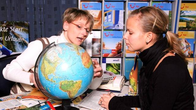 Zwei Frauen betrachten einen Globus.