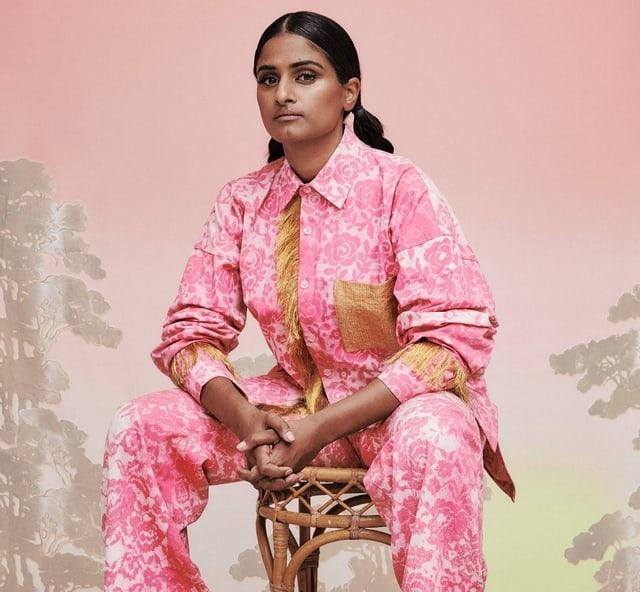 Priya Ragu sitzt auf einem Stuhl