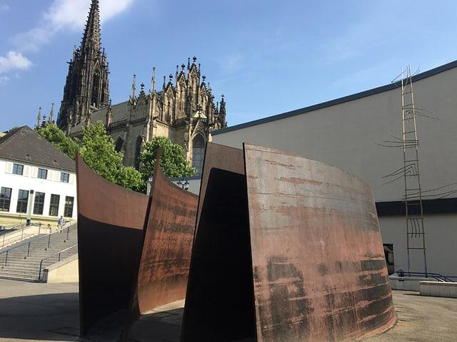 Kunstwerk aus Metall, hinten eine grosse Kirche.