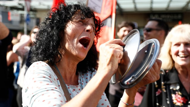 Eine Frau demosntriert mit Pfannendeckeln gegen das Umfahrungsprojekt Westast.