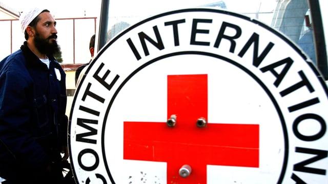 Ein afghanischer Mann steht neben dem Schild des Internationalen Komitees des Roten Kreuzes in Kabul.