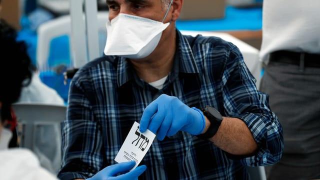 Ein Mann mit Maske hält einen Wahlzettel in der Hand.